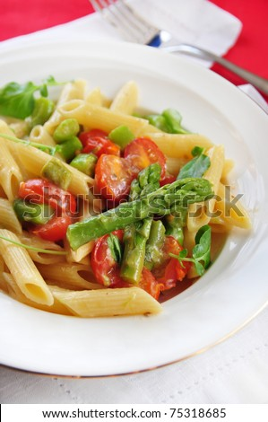 pasta penne with asparagus and tomatoes - stock photo
