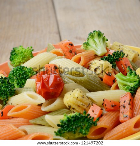 Pasta Penne With Broccoli Carrot Corn And Tomatoes On The Wooden Table