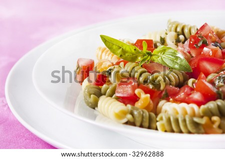 Pasta primavera garnished with basil leaves - stock photo