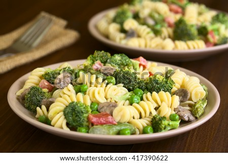 Pasta primavera with green asparagus, pea, broccoli, mushroom and tomato in cream sauce, photographed with natural light (Selective Focus, Focus in the middle of the pasta on the first plate)