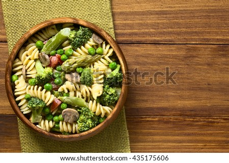 Pasta primavera with green asparagus, pea, broccoli, mushroom and tomato in cream sauce served in wooden bowl, photographed overhead on dark wood with natural light - stock photo