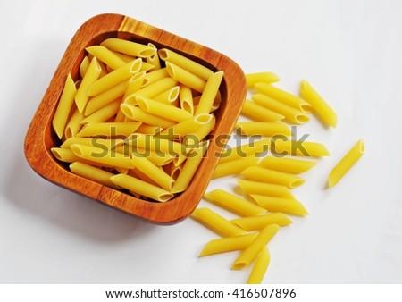 Pasta. Raw penne pasta. Penne pasta. Italian penne rigate macaroni pasta. Raw pasta in wooden bowl on white background. - stock photo