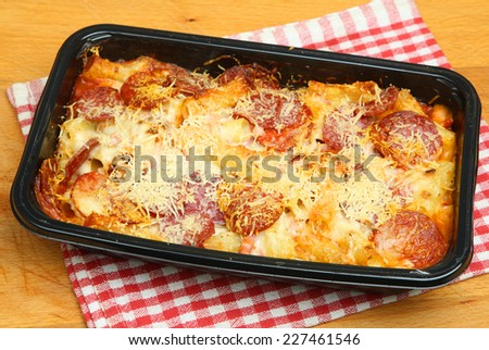 Pasta ready meal with salami sausage, ham and cheese. - stock photo