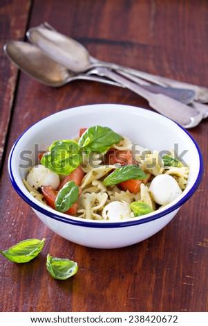 Pasta salad Caprese style with farfalle, tomato and mozarella - stock photo