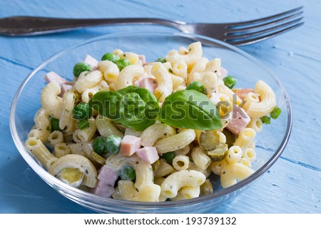 Pasta salad in a glass bowl on blue wood.