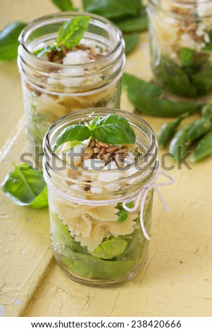 Pasta salad in jars with farfalle, salad greens, peas and feta - stock photo