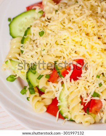 pasta salad with cheese, tomato and cucumber - stock photo