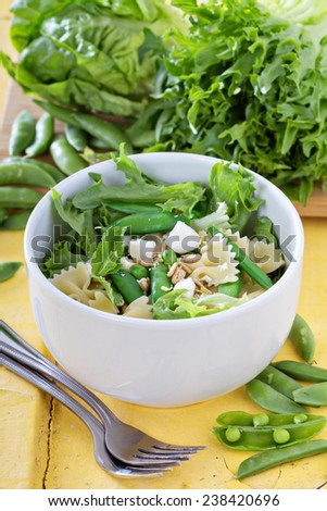 Pasta salad with farfalle, salad greens, peas and feta