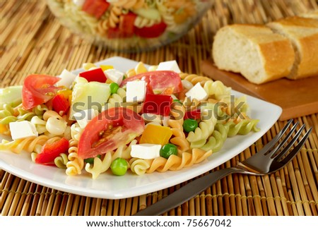Pasta salad with fresh vegetables (tomato, pea, bell pepper, cucumber) and cheese on plate with fork next to it and baguette in the back (Selective Focus, Focus on the front of the salad) - stock photo