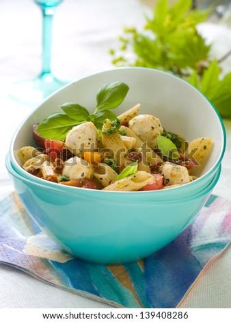 Pasta salad with mozzarella and tomato for picnic, selective focus - stock photo