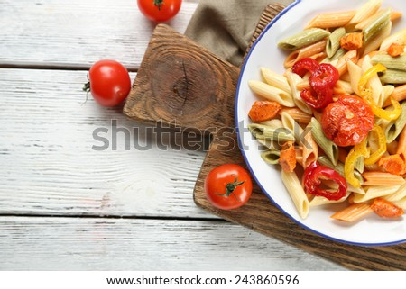Pasta salad with pepper, carrot and tomatoes on wooden table background - stock photo