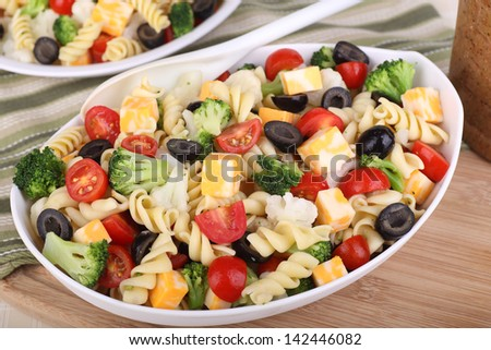 Pasta salad with tomato, broccoli, black olives, cauliflower and cheese in a bowl - stock photo