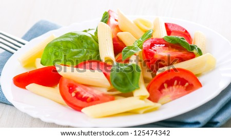 Pasta salad with tomatoes and fresh basil leaves
