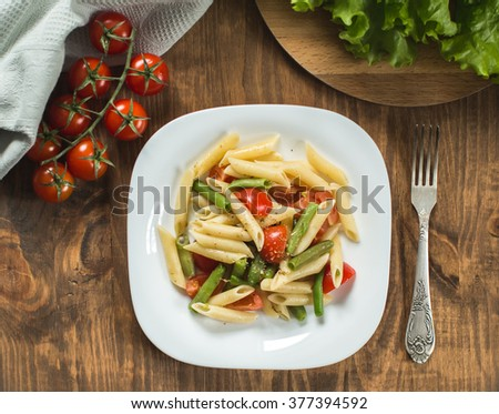 Pasta salad with  tomatoes on the kitchen table, top view - stock photo