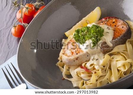Pasta salmon fresh seasoning pasta with grilled salmon steak in a decor dish - stock photo