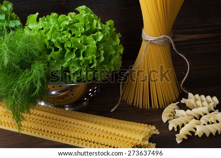 Pasta spaghetti  on wooden table with greens in a colander - stock photo