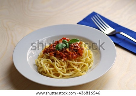Pasta. Spaghetti. Tasty homemade spaghetti pork sauce on white plate and fork with blue napkin on a rustic wooden table, basil green leaves, ready to served. - stock photo