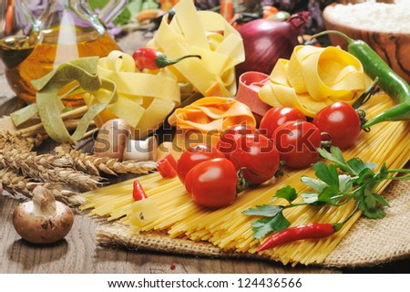 Pasta spaghetti, vegetables and spices, on wooden table - stock photo