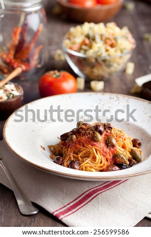 Pasta spaghetti with tomato sauce, capers and olives on a wooden background. Traditional Italian food.  - stock photo