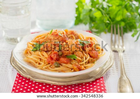 Pasta spaghetti with tuna, capers and parsley in tomato sauce. Selective focus - stock photo