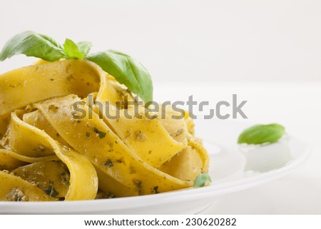 Pasta tagiatelle with pesto on white woodboard - stock photo
