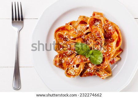 Pasta tagiatelle with tomato on white woodboard