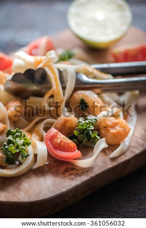 Pasta tagliatelle and shrimp on wooden board,selective focus