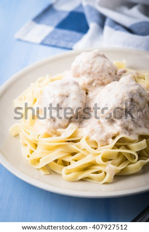 Pasta tagliatelle with meatballs and creamy sauce on blue wooden background close up. Italian cuisine. - stock photo