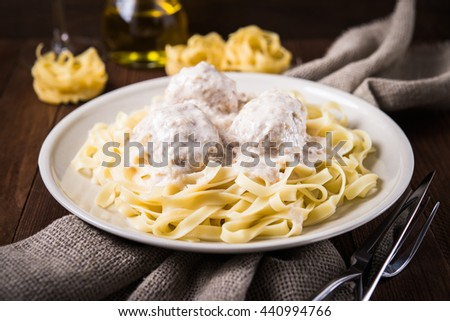 Pasta tagliatelle with meatballs and creamy sauce on dark wooden background close up. Italian cuisine. - stock photo