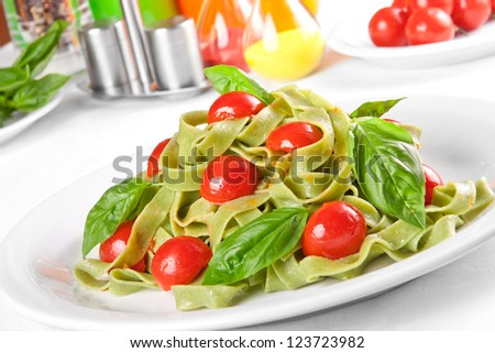 Pasta tagliatelle with pesto sauce and cherry tomato - stock photo