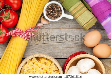 Pasta, tomatoes, mushrooms and eggs on wooden table background with copy space