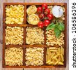 Pasta variety in a compartment box with garlic, tomatoes and basil - stock photo