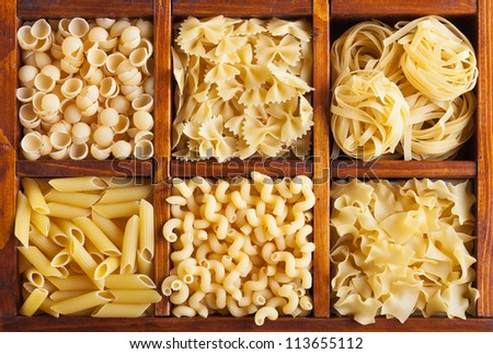 Pasta variety in wooden compartment box - top view - stock photo