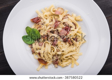 pasta with bacon and mint on white plate at dark wood table - stock photo