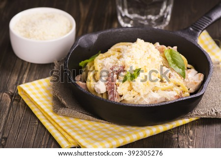 Pasta with bacon, chicken, parmesan and scrambled egg. Selective focus - stock photo