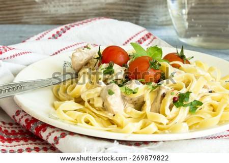 Pasta with bechamel sauce and cherry tomato. - stock photo