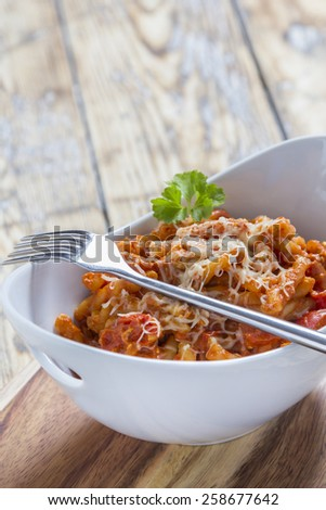 Pasta with bolognese and cheese in a modern white bowl - stock photo