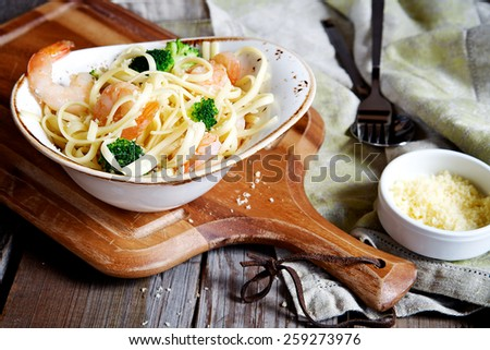Pasta with broccoli and prawns on a plate on a wooden background - stock photo