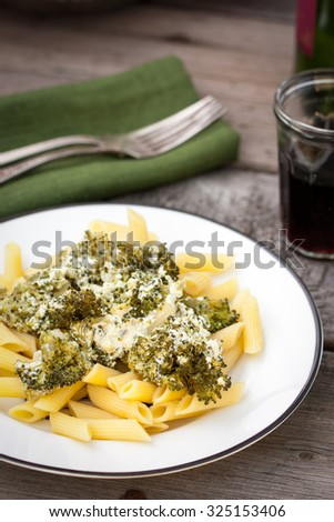 Pasta with broccoli, stewed in cream on a wooden table