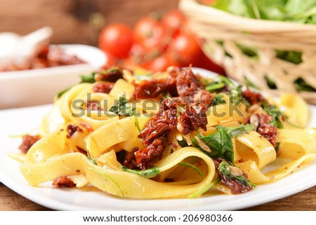 pasta with dry tomatoes and rucola - stock photo