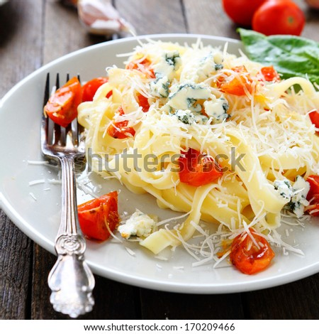 pasta with grated parmesan cheese and tomatoes, food closeup - stock photo
