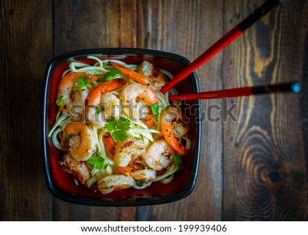 Pasta with grilled shrimps on wooden background - stock photo