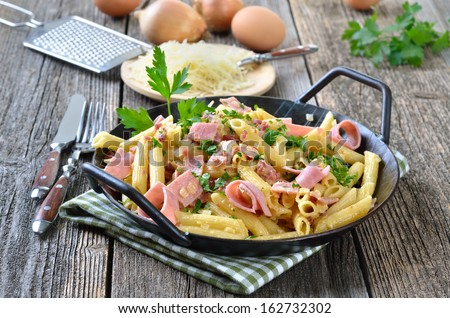 Pasta with ham and bacon, cheese and eggs in a pan - stock photo