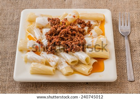 Pasta with meat and tomato sauce on linens napkin - stock photo