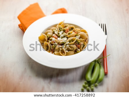 pasta with mozzarella fresh peas and tomatoes - stock photo