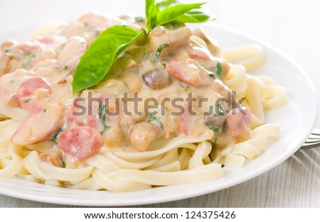 Pasta with mushrooms, smoked sausage and cream sauce - stock photo