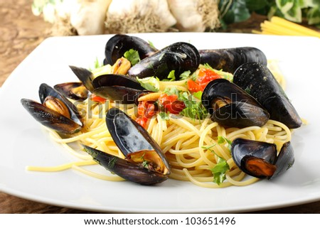 Pasta with mussels and cherry tomatoes on complex background