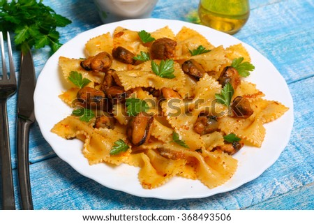 pasta with mussels and parsley on a wooden background - stock photo