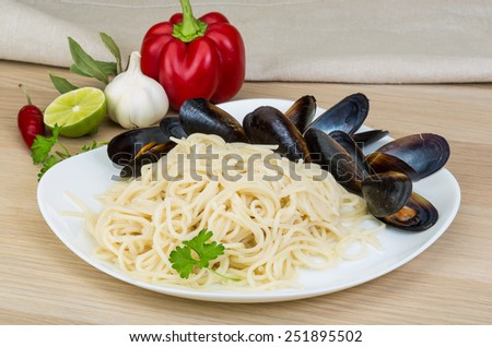 Pasta with mussels on thw wooden background - stock photo