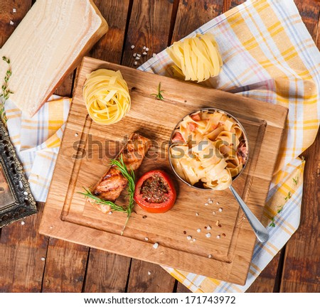 Pasta with parmesan, tomato and grilled salmon on wooden board - stock photo